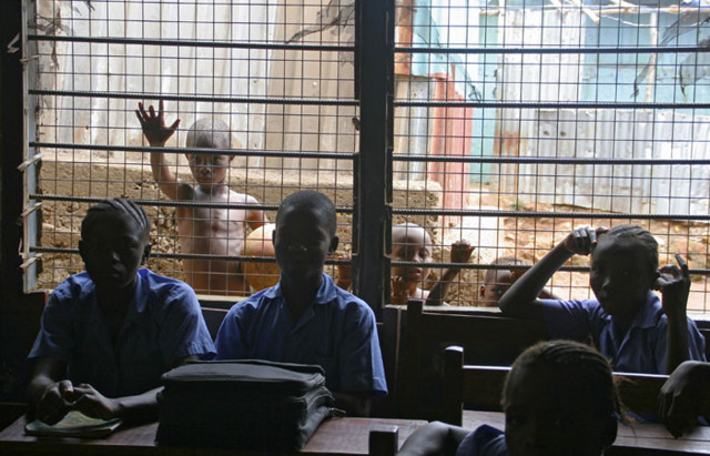 Children look in to a classroom in a Freetown slum.