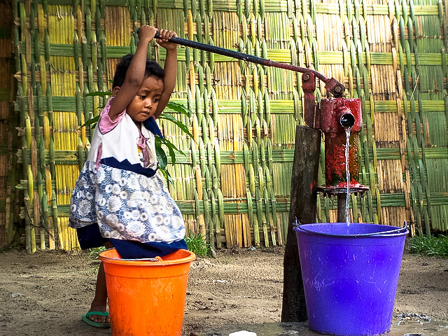 Gril pumps water from well Madagascar photo