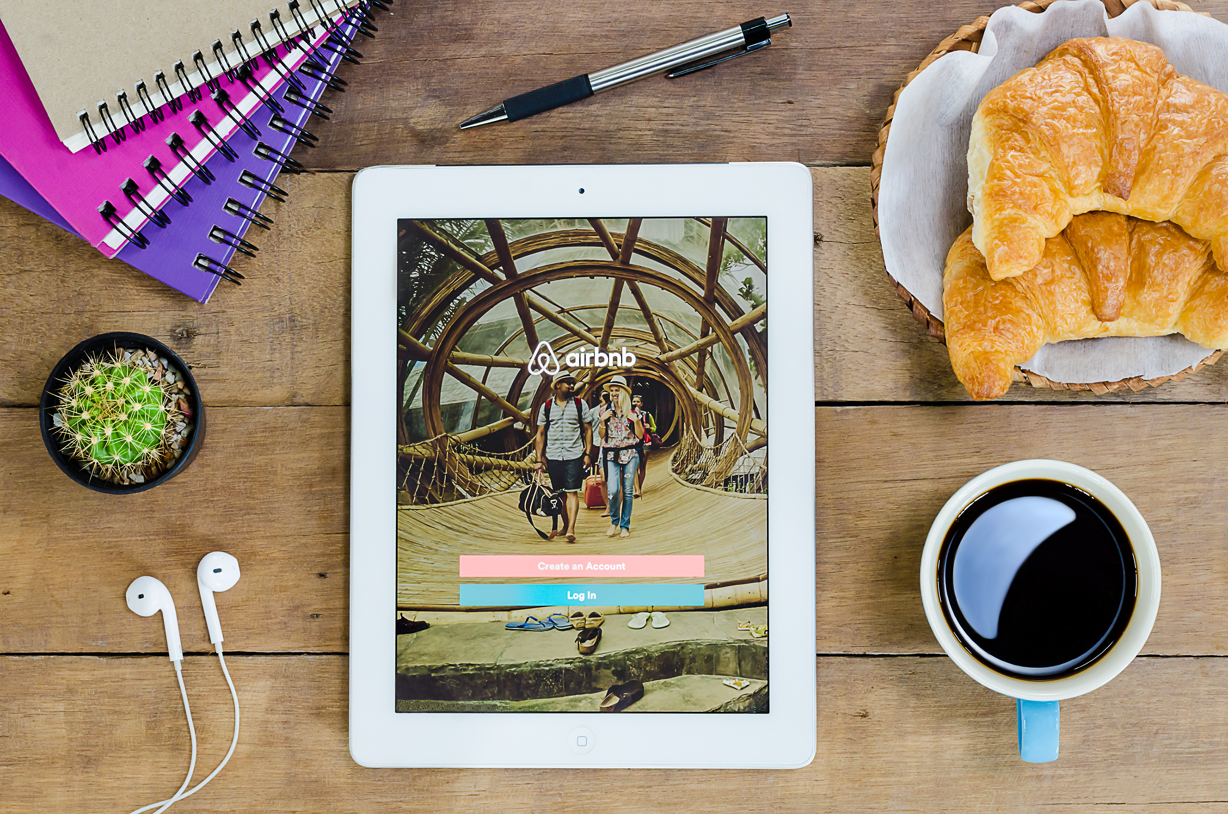 Airbnb app on tablet sitting on table with coffee and croissants